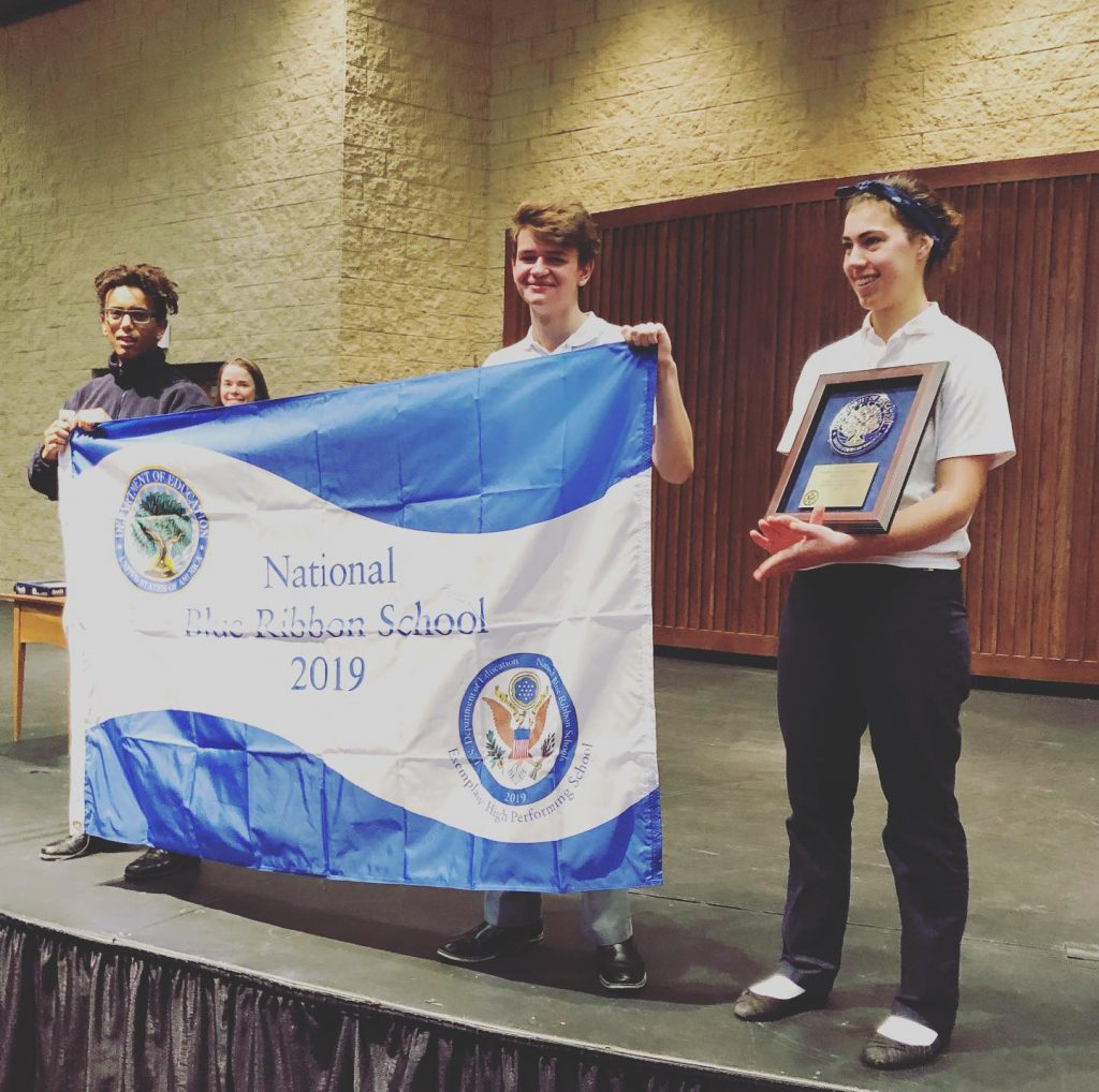 Three Trinity students hold the Blue Ribbon award and a flag celebrating it.